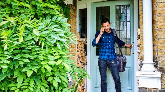 Transgender male at the door talking on mobile phone