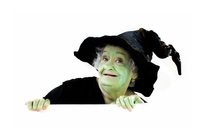 Older woman in witch makeup (green face) and witch (black pointy) hat