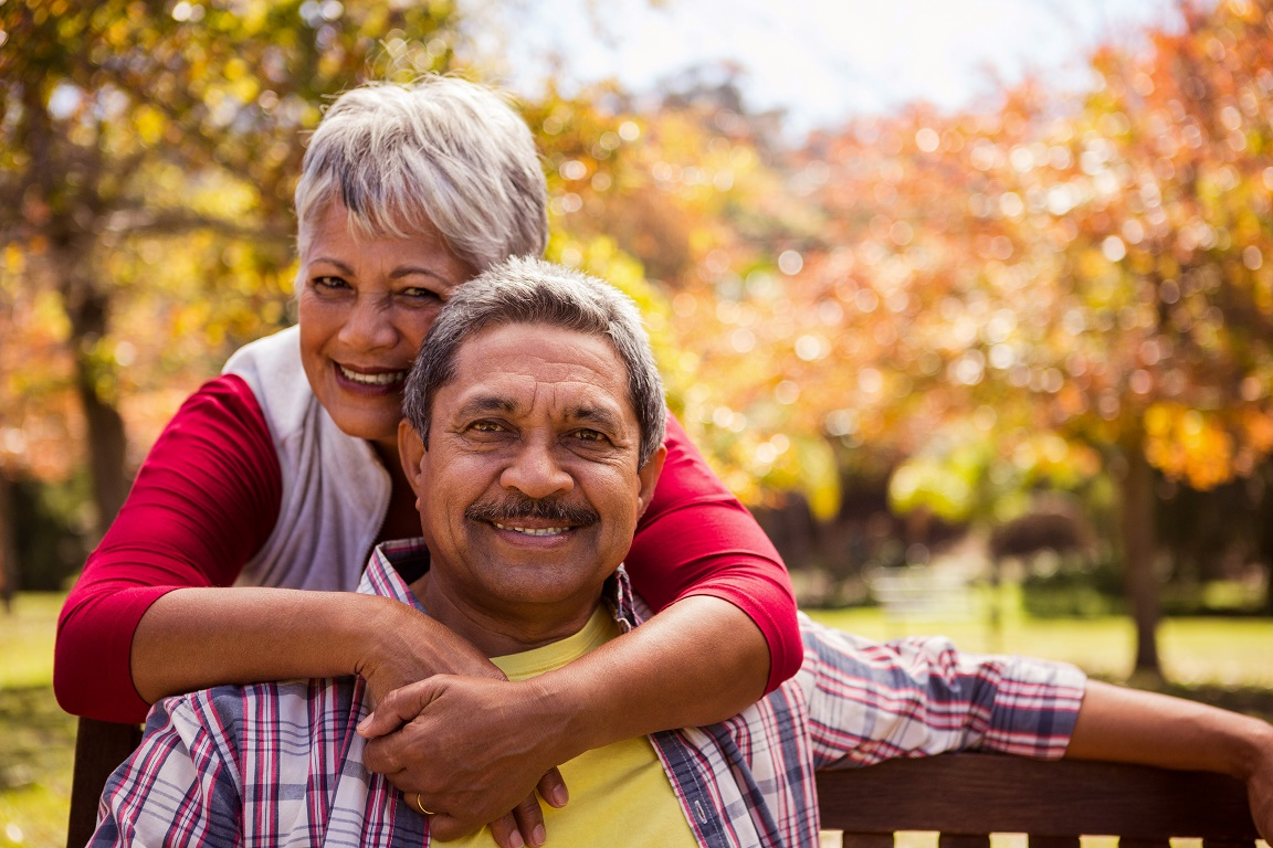 Woman embracing man sitting on a bench outside and it's Fall, both facing forward smiling