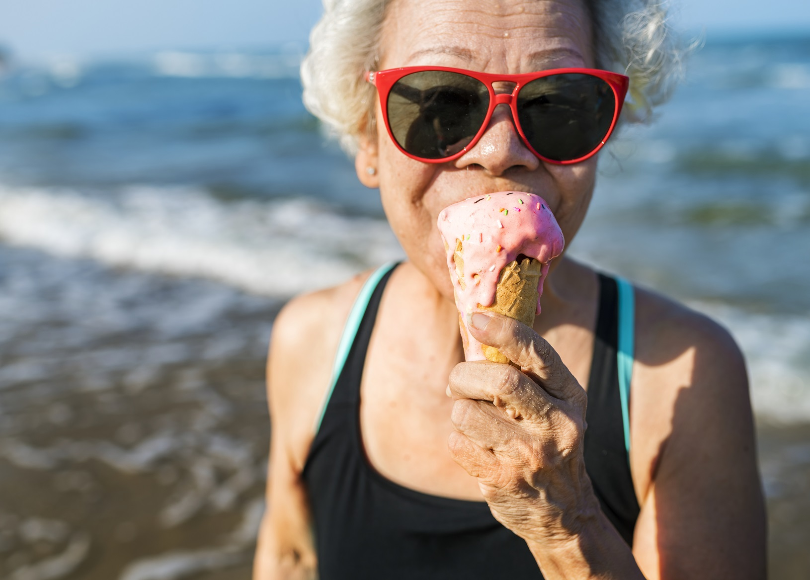 Older woman in sunglasses eating ice cream on the beach