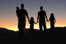 Silhouettes of a family with a sunset in the background.