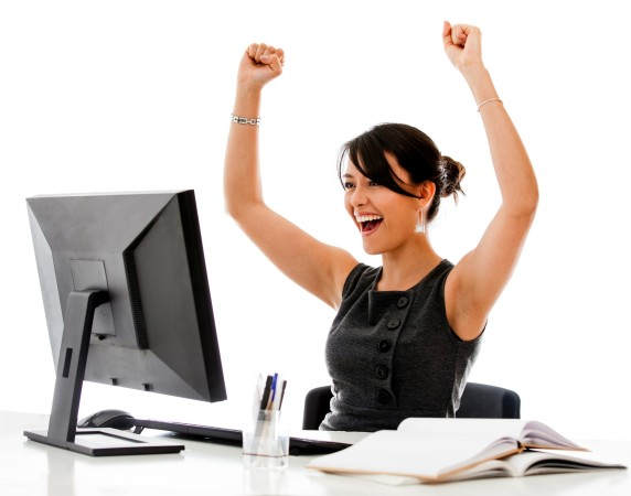 woman smiling with raised arms in celebration, sitting at laptop